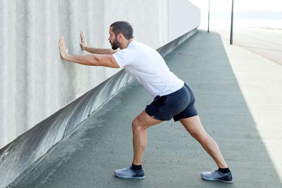 A man using a wall to stretch his hips and calves.